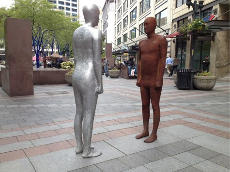 two statues of humans having a staring contest