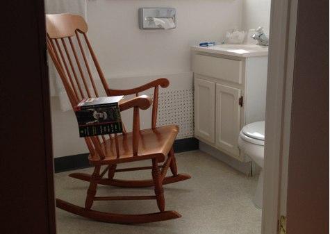 a rocking chair in a motel bathroom